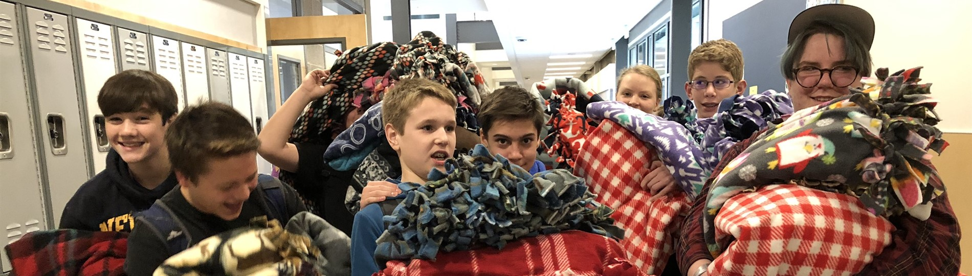 Students carry blankets they made for Winter Hospitality Overflow